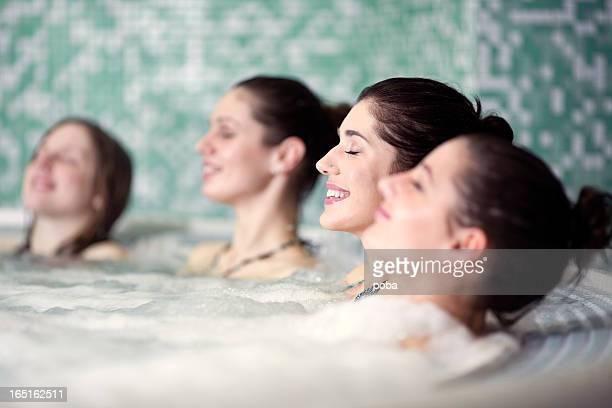 Amis de se détendre dans le jacuzzi au centre de remise en forme et spa