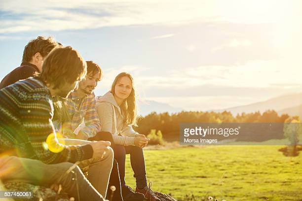 Friends relaxing on field