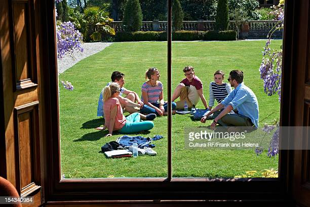 Friends relaxing on manicured lawn