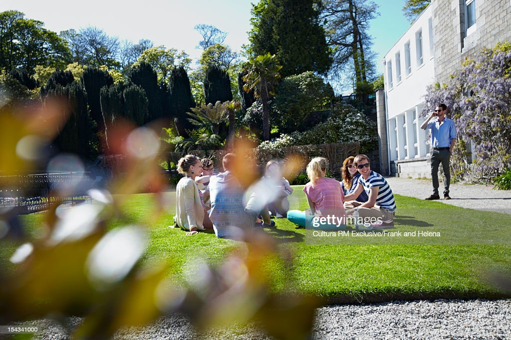Friends relaxing on manicured lawn : Stock Photo