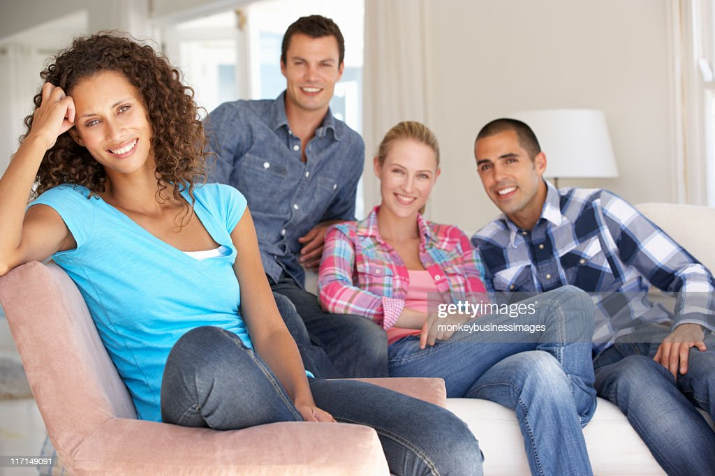 Friends Relaxing On Sofa At Home Together : Stock Photo