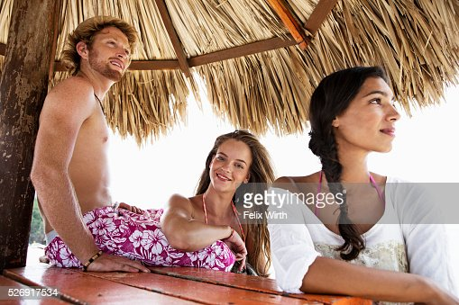 Friends relaxing under sunshade : Stock-Foto