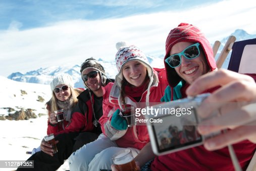 friends relaxing with drinks on ski slope : Stock Photo