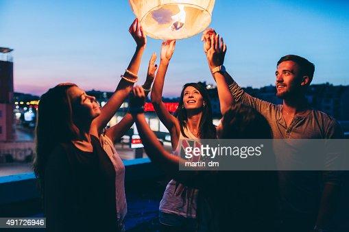 Friends releasing paper lantern