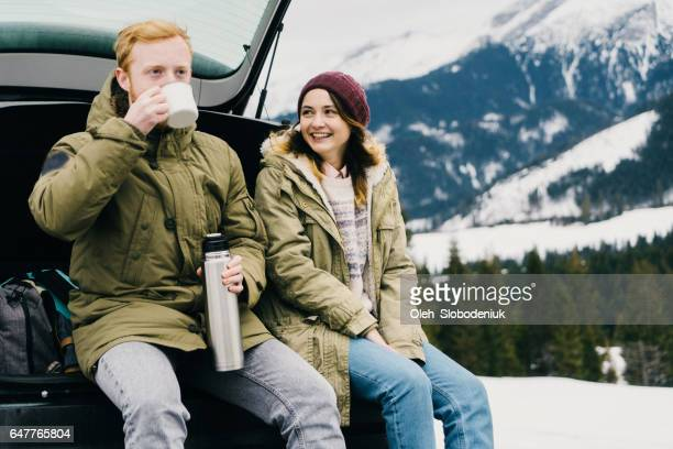 Friends resting and drinking hot drink near the car in mountains