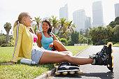 Friends resting in park after rollerblading