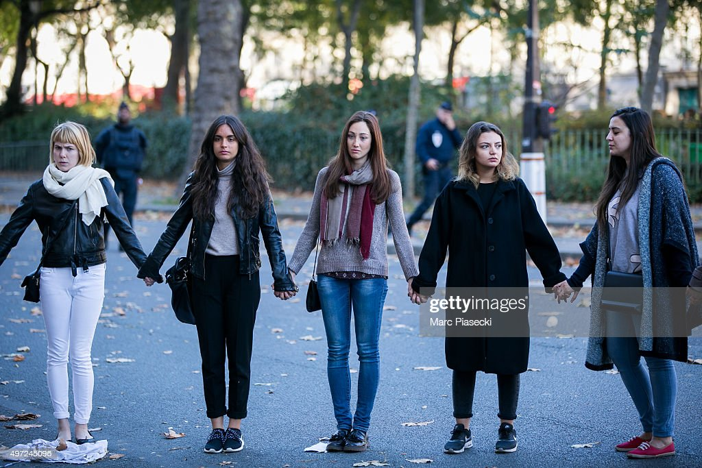 Friends reunite in memory of a victim near 'Le Bataclan' theatre on Boulevard Voltaire following Fridays terrorist attack and France observes three days of national mourning on November 15, 2015 in Paris, France. As France observes three days of national mourning members of the public continue to pay tribute to the victims of Friday's deadly attacks. A special service for the families of the victims and survivors is to be held at Paris's Notre Dame Cathedral later on Sunday.