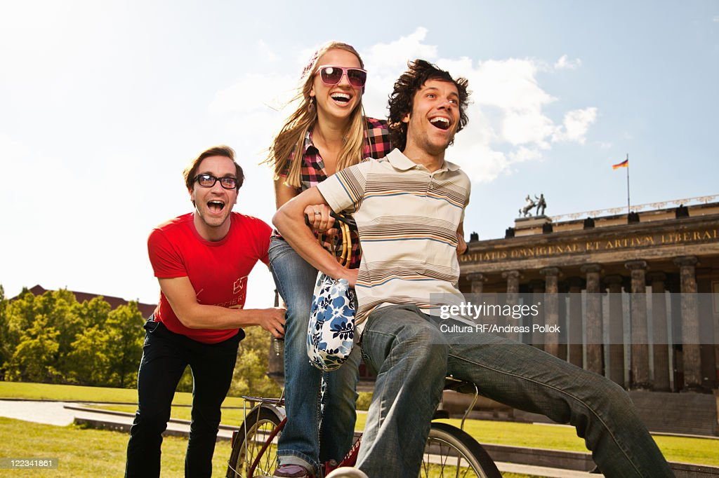 Friends riding bike together in park : Stock Photo
