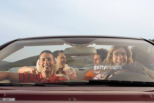 Friends Riding in Convertible on Desert Road Trip