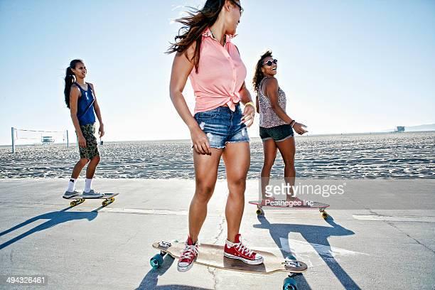Friends riding longboards on beach