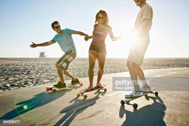 Friends riding longboards on beach