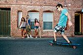 Friends riding longboards on city street