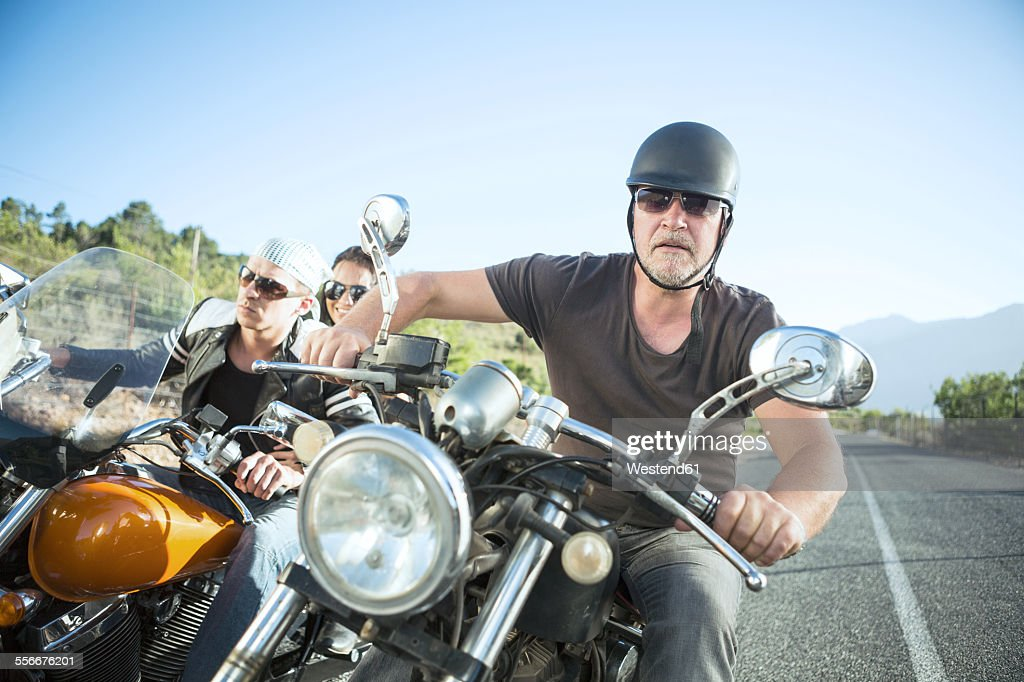 Friends riding motorcycles on open road