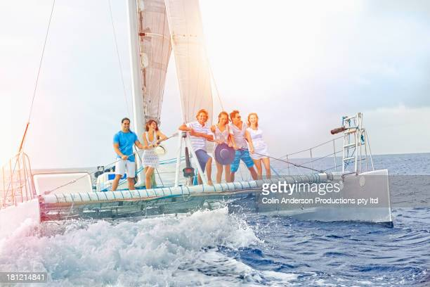 Friends riding sail boat on waves