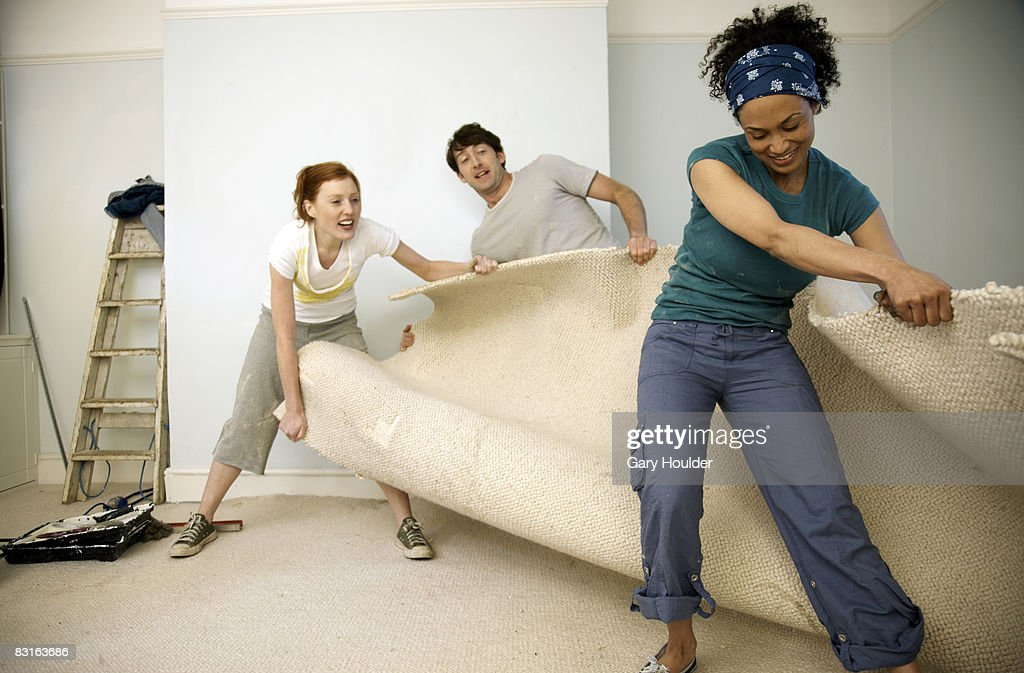 Friends ripping away an old carpet : Stock Photo