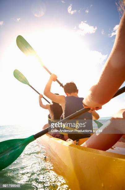 Friends rowing canoe in ocean