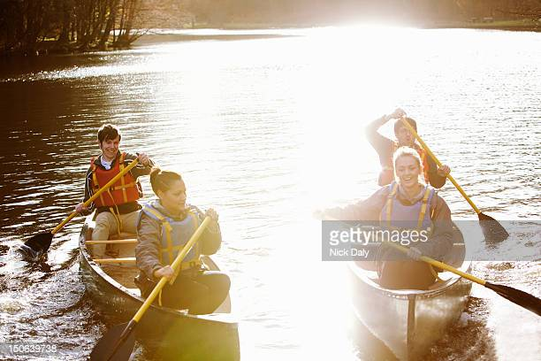 Friends rowing canoes on still lake