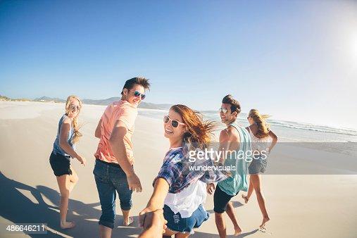 Amigos correr ao longo da praia