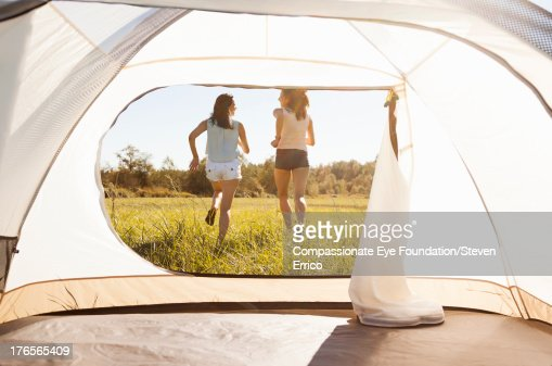 Friends running by tent in field : Stock Photo