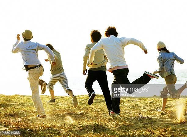 Friends Running In Grassland