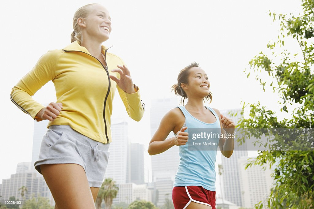 Friends running in urban park : Stock Photo