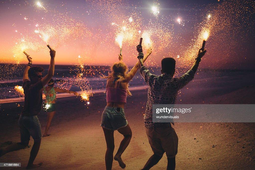 Amis courir sur la plage avec feux d'artifice : Photo