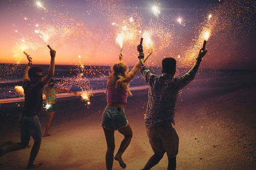 Friends running on a beach with fireworks