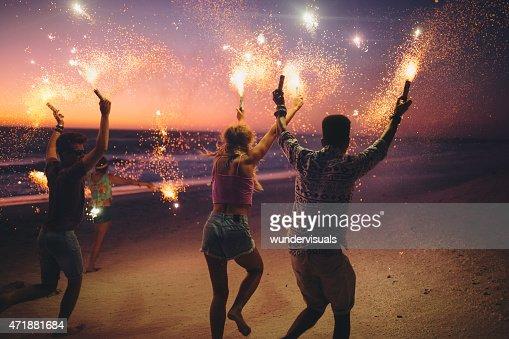 Amis courir sur la plage avec feux d'artifice