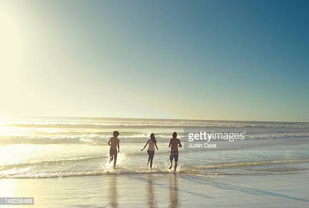 3 friends running out in the ocean