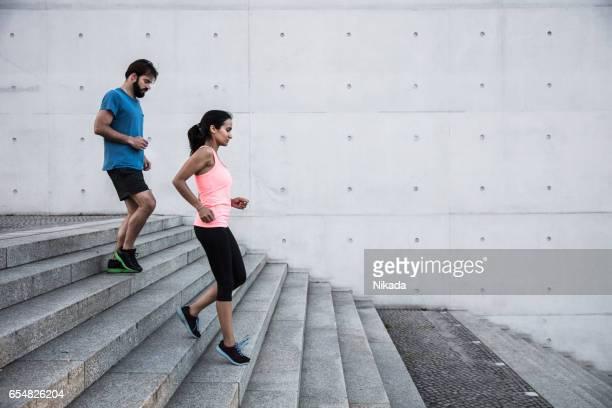 friends running steps down in urban setting