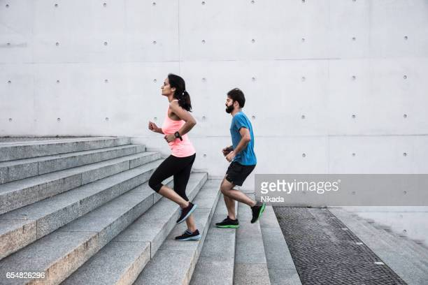 friends running steps up in urban setting