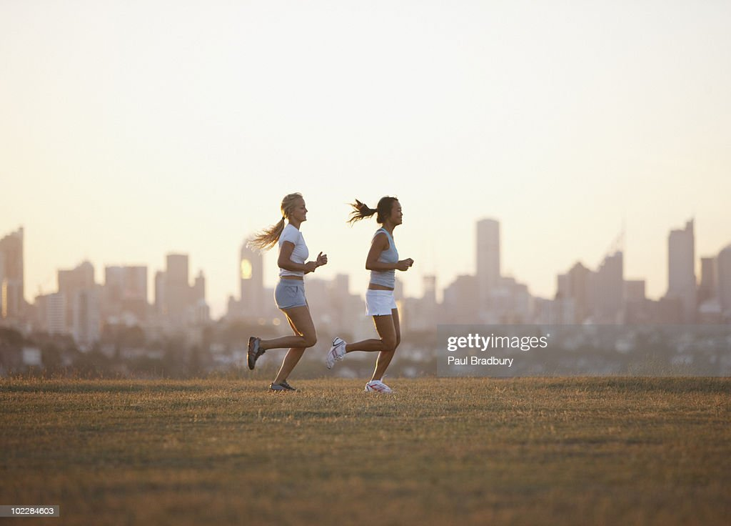 Friends running through field : Stock Photo