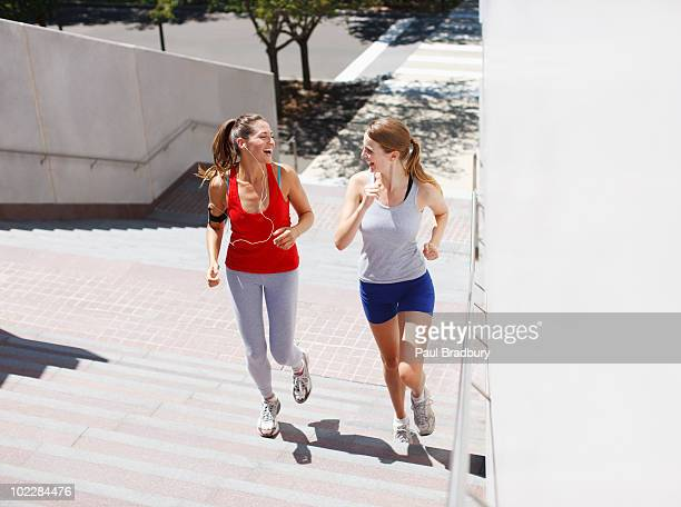 Friends running up urban staircase