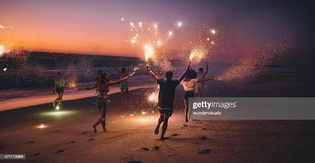 Friends running with fireworks on a beach after sunset : Stock Photo