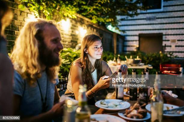 Friends Sat Together Talking And Drinking After Barbecue