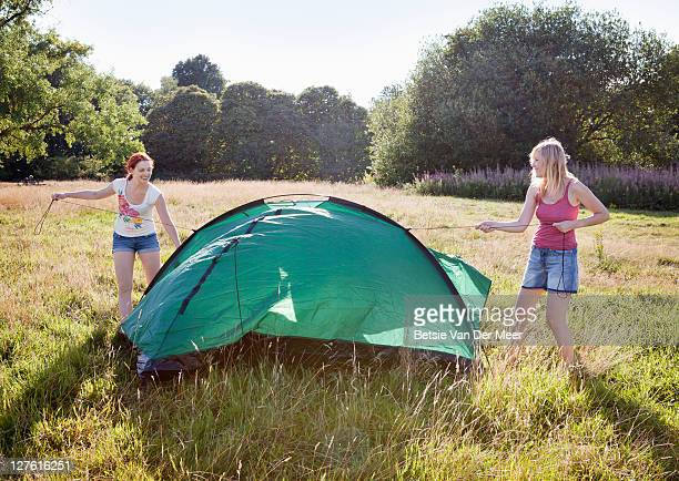 friends setting up a tent in a field.