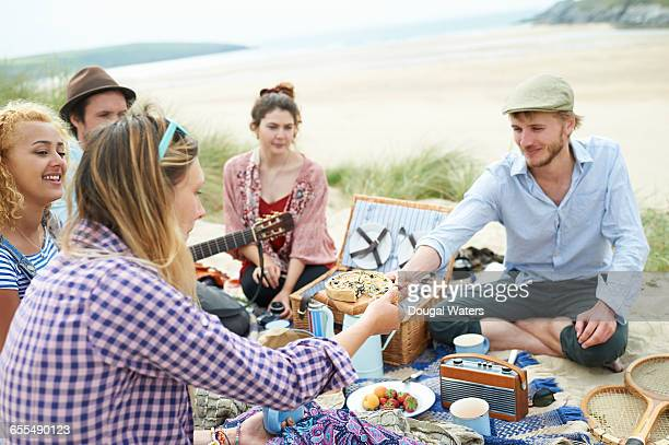 Friends share food around a beach picnic.