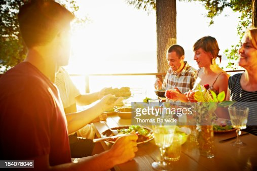 Friends sharing a meal on deck of cabin at sunset : Stock Photo