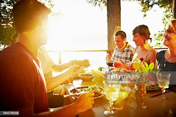 Friends sharing a meal on deck of cabin at sunset