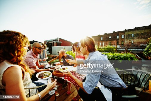 Friends sharing dinner on rooftop garden deck