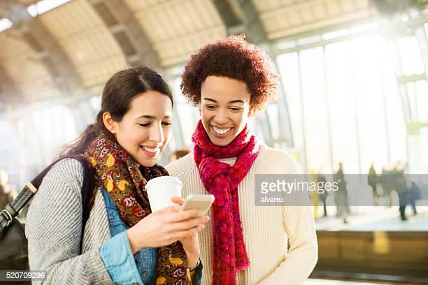Amigos intercambio de mensajes en su teléfono inteligente