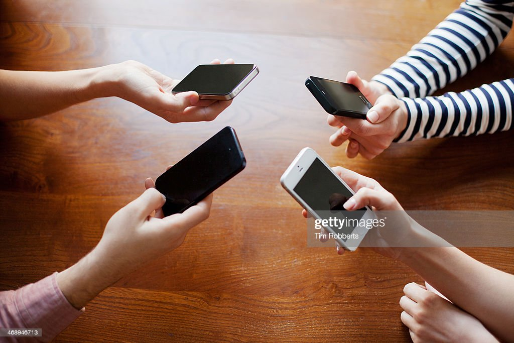 4 friends sharing on smart phones. : Stock Photo