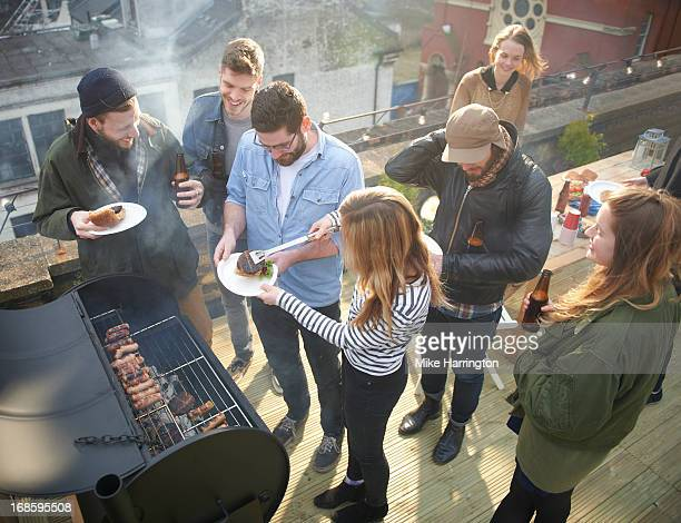 Friends sharing sausages in roof garden.