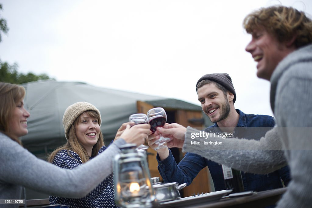 Friends sharing toast over wine while glamping. : Stock Photo