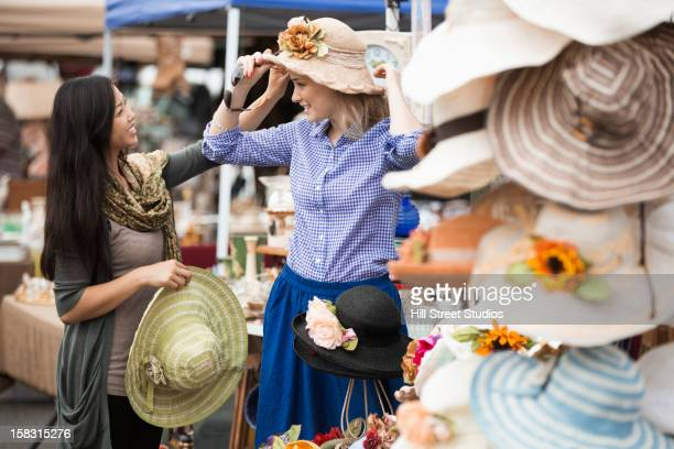 Friends shopping for hats at flea market