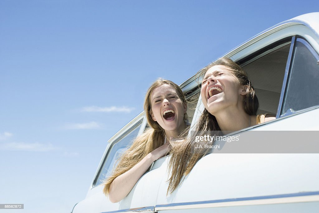 Friends shouting out car window : Stock Photo