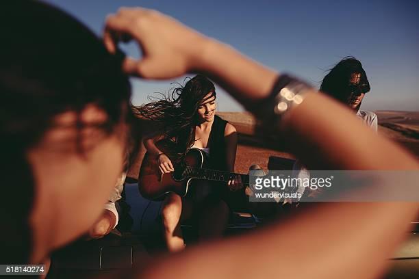 Amis chantant et dansant sur route voyage avec une guitare
