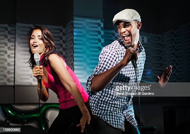 Friends singing karaoke in nightclub
