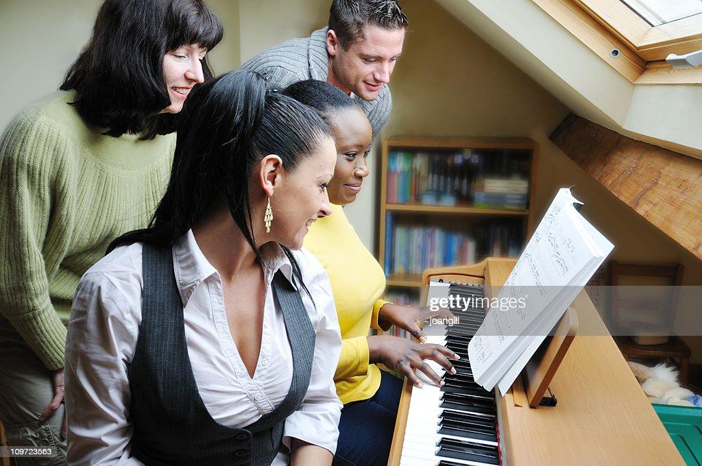 friends singing together round keyboard