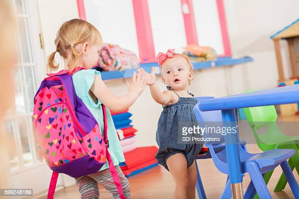 Friends, sisters high five in daycare classroom